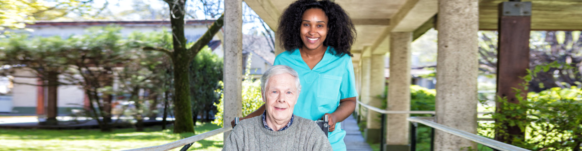 caregiver and senior patient on wheelchair smiling