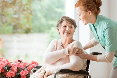 caregiver hugging senior woman from behind