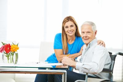 caregiver assisting senior man in eating